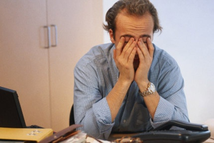 MAIN_196-Man-covering-face-in-office